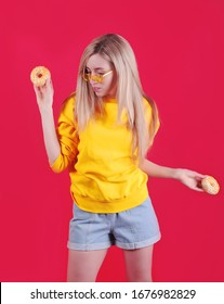 Blond woman with donats posing on red background.
