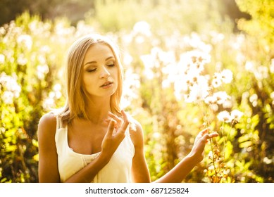 Blond woman dreaming and relanxig on sunset herbs meadow during sun light. backlit. wild autumn field with spring flowers. summertime season. blondy girl enjoy sun warm with closed eyes