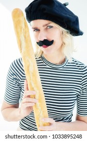 blond woman dressed as a french man with mustache and beret holding a baguette