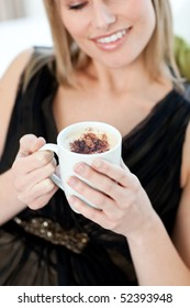 Blond woman drinking a coffee sitting on a sofa at home