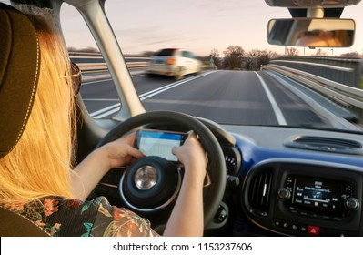 blond woman driving the car, at the same time who writes a text message on your smartphone