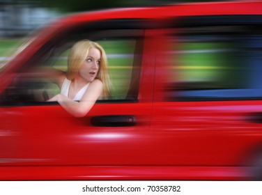 A blond woman is driving a car with a zoom speed effect. She is turning her head and not looking at the road.