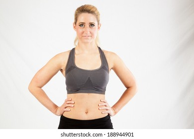 Blond woman in exercise outfit with bare midriff, standing looking at the camera with her hands on her hips