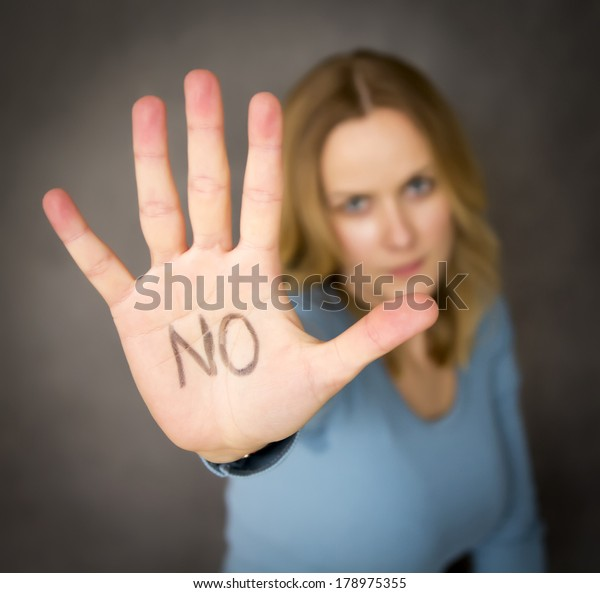 Blond woman expressing denial with NO written on her hand