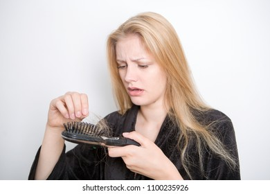 Blond woman finding hair in her hairbrush