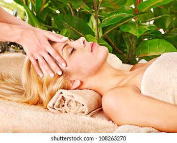 Blond woman getting facial massage in tropical beauty spa.