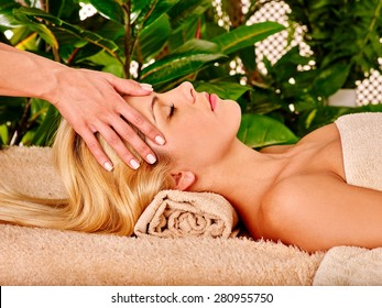 Blond woman getting facial massage in green tropical beauty spa.