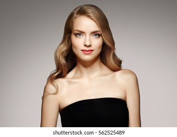 Blond Woman girl with long and shiny wavy hair . Beautiful model with curly hairstyle over dark background.