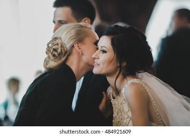 Blond woman greets a brunette bride