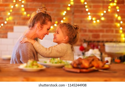 Blond woman and her little daughter hugging indoors on the light background