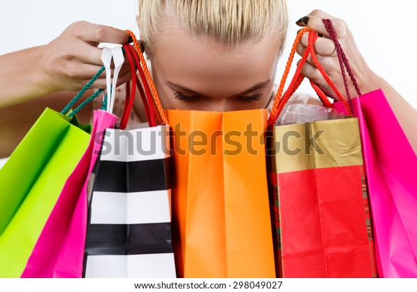 Blond woman inspecting content of colored paper bags with fresh buyings. Shopping, consumerism, delivery and present concept. Happy birthday and gifts concept