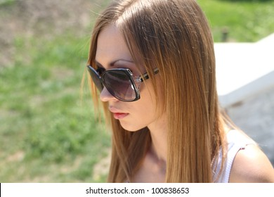 Blond woman in jeans and dark glasses standing on an outdoor summer patio