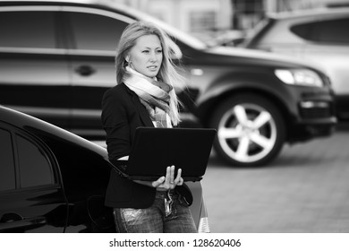 Blond woman with laptop on the car parking