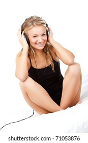 blond woman listening the music, sitting on bed