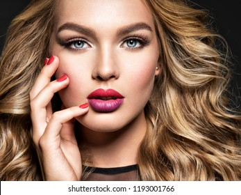 Blond woman with long curly beautiful hair. Fashion make-up. Fashionable girl. Red fingernails.   Gorgeous face of an attractive fashion model. Bright colored lips.