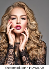 Blond woman with long curly beautiful hair. Makeup. Fashion make-up. Fashionable girl dressed in black dress. Closeup portrait. Gorgeous face of an attractive fashion model. Bright red lips.