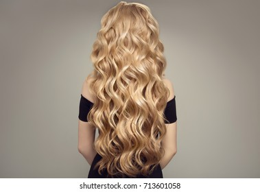Blond woman with long curly beautiful hair. Back view.