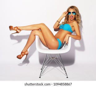 blond woman with long hair in blue underwear sitting on chair, over white background