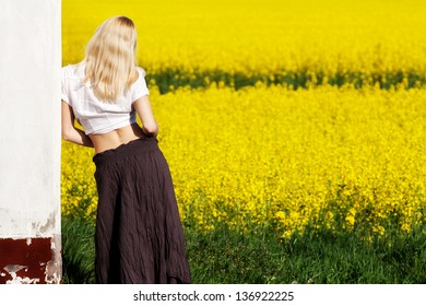Blond woman looking at the rapeseed field