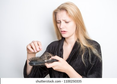 Blond woman losing hair finding it in a hairbrush