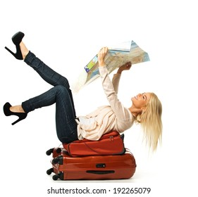 Blond woman lying on a suitcase with map