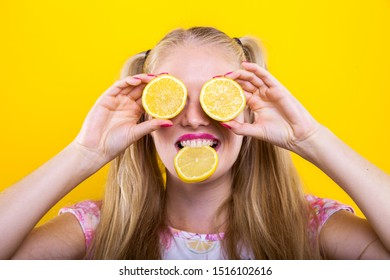 blond woman makes a funny facial expression with lemos slices on her eyes and in her mouth, which causes drooling saliva. the sour juice of this citrus fruit makes people enjoy freshness and vitamin c