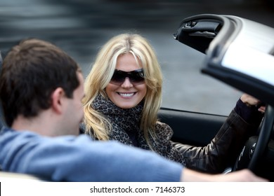 Blond woman and a man in a convertible car