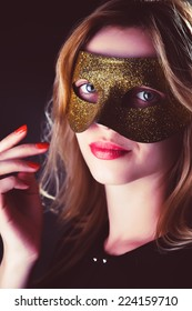 Blond Woman with Mask of Feathers in Low Key