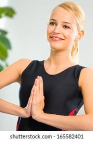 Blond woman meditating, indoors