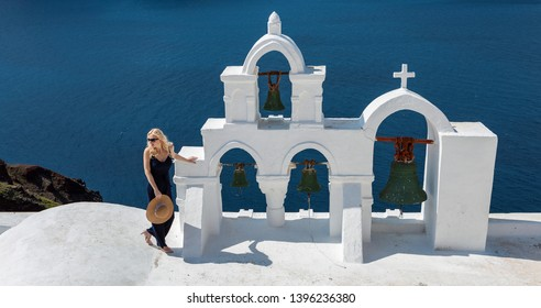 blond woman next to a Santorini bell tower in Oia, pointing at something in the distance