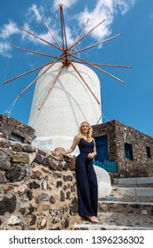 blond woman in Oia on Santorini in front of the famous windmill