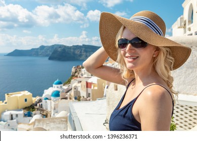 blond woman in Oia on Santorini with caldera view in the background