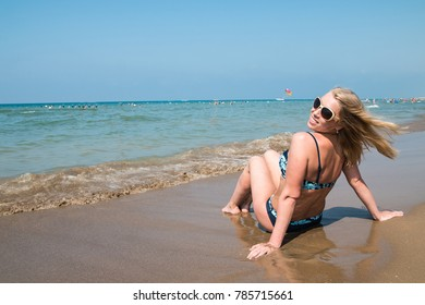 Blond woman on the beach in a water of the sea or ocean