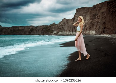 blond woman on a black beach on Santorini, with cliff in the background and a rough sea