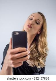Blond woman on a white background, on cellphone, taking selfie