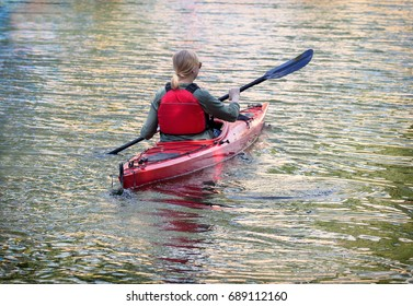 Blond woman paddles canoe on Stockholm's water