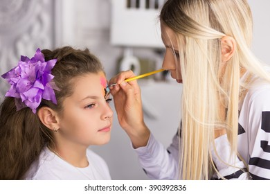 Blond woman paints the face of a girl