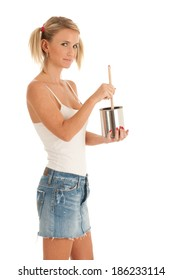 Blond woman in pig tails and cut off jeans skirt dips a paint brush into a can of paint. Studio shot, isolated on white background.