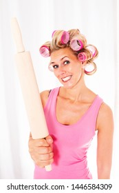 Blond woman with pink curlers holding a big rolling pin and smiles sarcastically