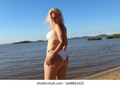 Blond woman posing for the camera at the beach with wwater in the background during vacation in the summer wearing a white bikini
