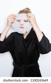 Blond woman putting a make-up mask on her face