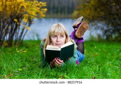 Blond woman reading the book on the grass