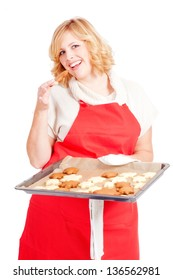 blond woman with red apron present christmas cookies on a  baking tray