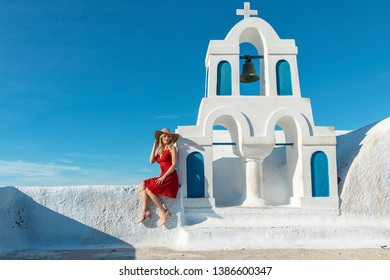 blond woman in a red dress sitting on a wall next to a small church bell tower
