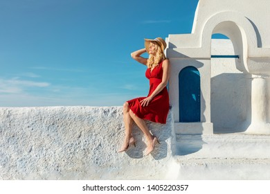 blond woman in a red dress sitting on a wall next to a small church bell tower, enjoying the sunlight
