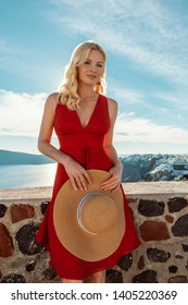 blond woman in a red dress and a sun hat in Oia on Santorini