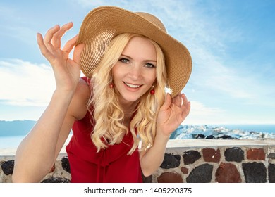 blond woman in a red dress and a sun hat in Oia on Santorini, coming closer to the camera