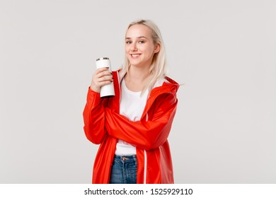 Blond woman in a red raincoat holding white thermal mug with hot beverage isolated over white background. Get ready for rainy cold days