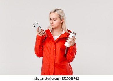 Blond woman in a red raincoat holding white thermal mug with hot beverage and smartphone standing isolated over white background.