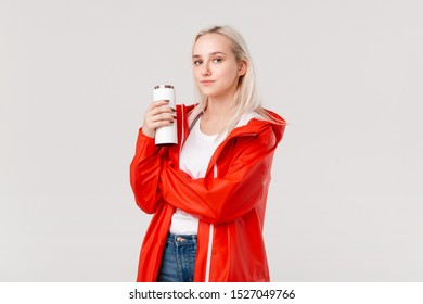 Blond woman in a red raincoat holding white thermal mug with hot beverage isolated over white background. Rainy cold days